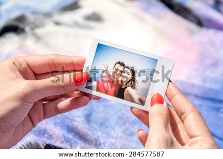 Girl Holding In Hands Instant Photo Of Young Happy Couple - stock photo