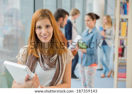 Girl holding laptop with group of students in college library - stock photo