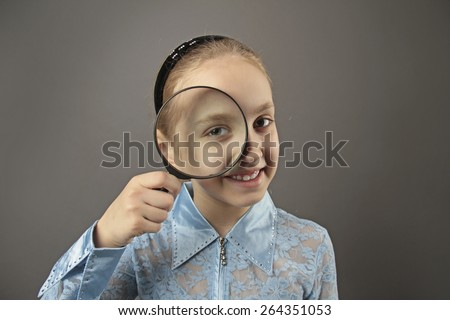 girl holding magnifying glass - stock photo
