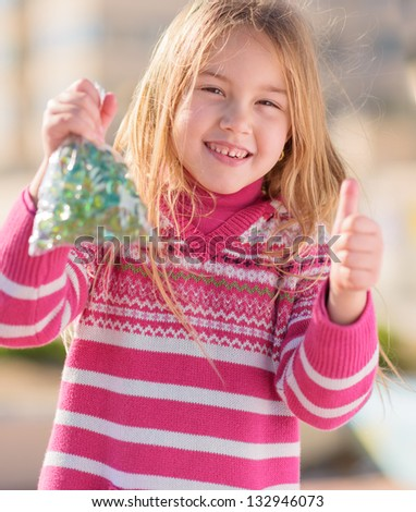 Girl Holding Marble And Showing Thumb Up, Outdoors - stock photo