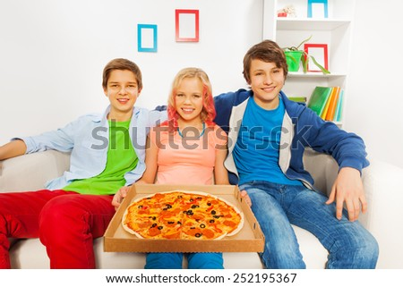 Girl holding pizza on carton and boys sitting near - stock photo