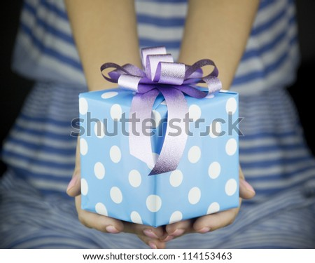 girl holding present box with ribbon bow - stock photo