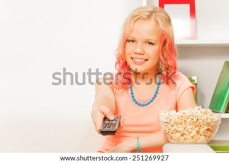 Girl holding remote control and bowl with popcorn - stock photo