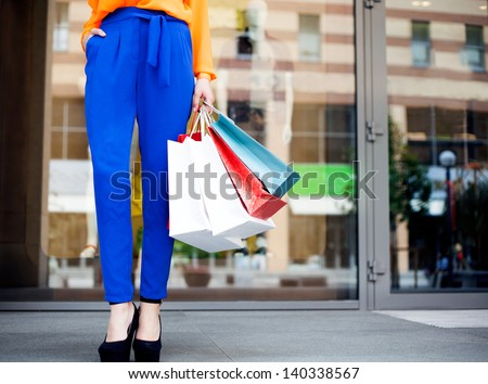 Girl holding shopping bags in one hand, legs in blue trousers - stock photo
