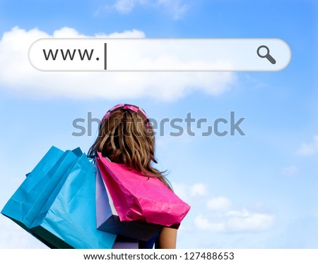 Girl holding shopping bags with address bar above against a blue sky - stock photo