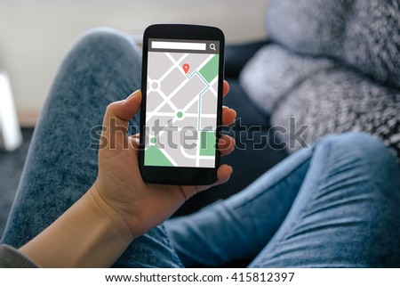 Girl holding smart phone with map gps navigation application on screen. All screen content is designed by me - stock photo