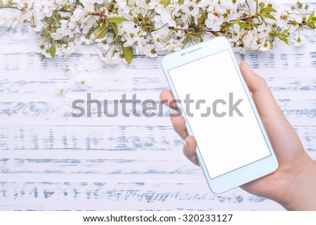 Girl holding the phone and photographed flowers. Mobile technology. Mobile Photography - stock photo