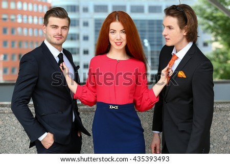 girl holding two young men tie - stock photo