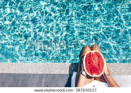 Girl holding watermelon in the blue pool, slim legs, instagram style. Tropical fruit diet. Summer holiday idyllic. - stock photo