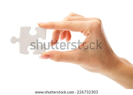 Girl holding white puzzle on a white background - stock photo