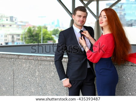 girl holding  young men tie - stock photo