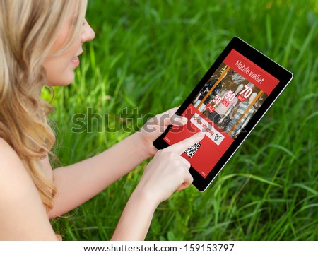 girl holds a tablet on a background of green grass and makes online shopping - stock photo
