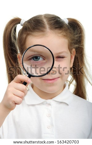 Girl holds in his hand a magnifying glass - stock photo