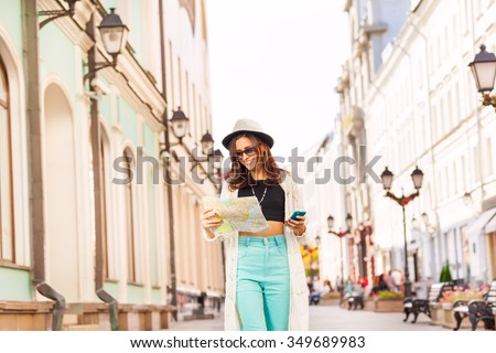 Girl holds mobile phone and city map on the street - stock photo
