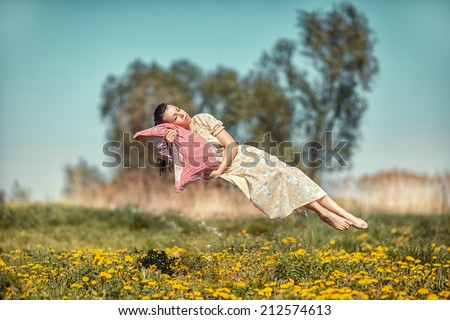 Girl hovers and sleeps on a pillow over a beautiful meadow. - stock photo