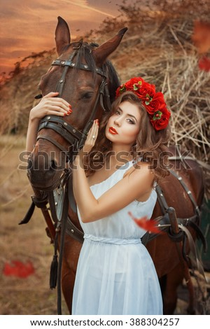 Girl hugging a horse's head. She is very beautiful in a white dress with a red wreath on his head. - stock photo