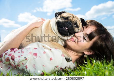 Girl hugging dog breed Mops - stock photo
