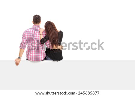 Girl hugging her boyfriend seated on a panel isolated on white background, rear view - stock photo