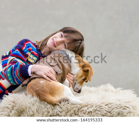 Girl hugging her dog in brown leather jacket - stock photo