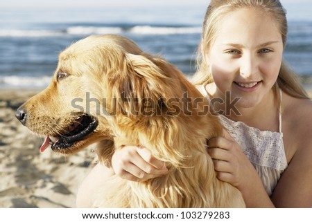 Girl hugging her dog on the beach and smiling at the camera. - stock photo