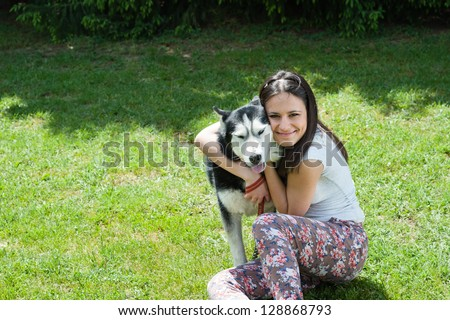girl hugging her dog siberian husky - stock photo