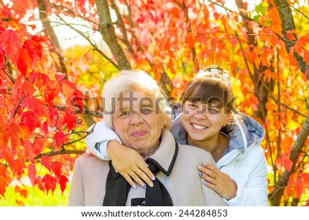 girl hugging her old grandmother in autumn park - stock photo