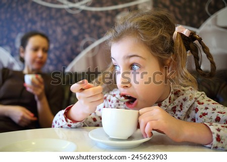 Girl hurriedly drinking tea with spoon while sitting at table in cafe - stock photo