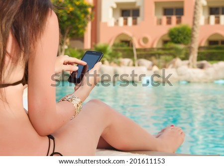girl in a bathing suit lying on a sun lounger by the pool with a mobile phone with isolated screen - stock photo