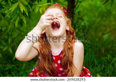 Girl in a beautiful dress in cherry garden - stock photo