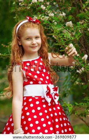 Girl in a beautiful dress near a flowering bush - stock photo