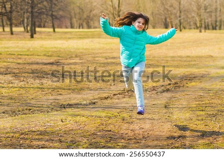 girl in a bright jacket and blue jeans running and jumping in a forest glade on a sunny day in early spring - stock photo