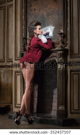 Girl in a crimson waistcoat, standing near the fireplace - stock photo