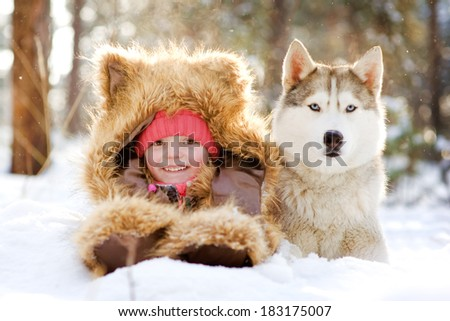 girl in a fur hat lying next to Husky in the snow in the forest - stock photo