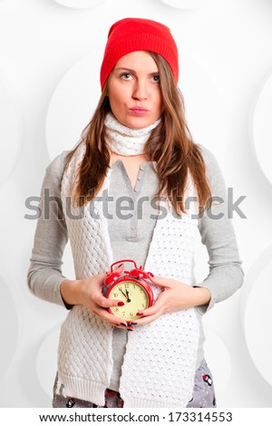 girl in a hat and scarf with red alarm clock - stock photo