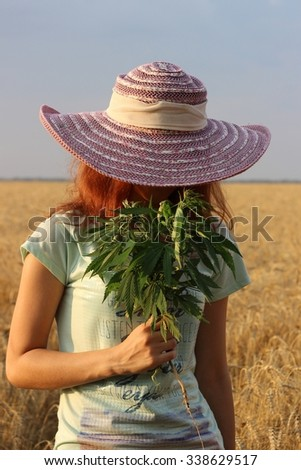 Girl in a hat on sunset in a wheat field with hemp cannabis in the hands - stock photo