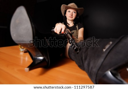 girl in a hat with a gun dark background - stock photo