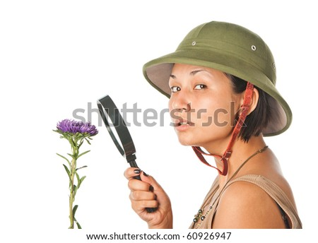 Girl in a pith helmet explores flower - stock photo