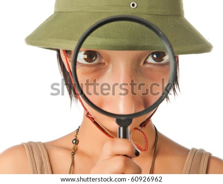 Girl in a pith helmet looks throught magnifier - stock photo