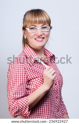 girl in a plaid shirt and points thinks and holds the pen in hand - stock photo