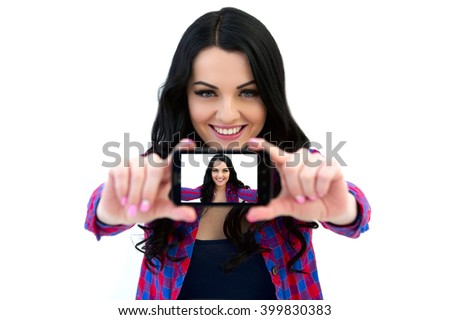Girl in a plaid shirt makes selfie. Portrait of a smiling cute woman making selfie photo on smartphone isolated on a white background - stock photo