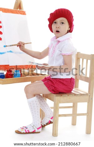 Girl in a red beret sits at an easel on a white background.The concept of a child's learning and development. - stock photo
