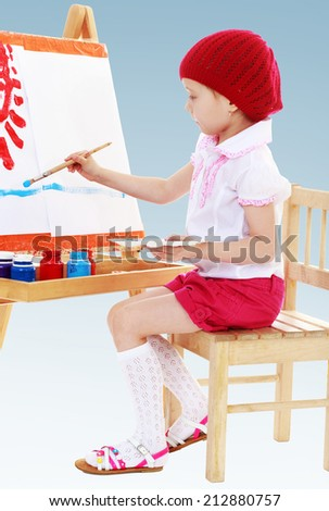 Girl in a red beret sits at his easel and paints the sun.The concept of a child's learning and development. - stock photo