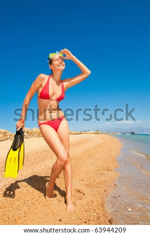 girl in a red bikini with a mask and flippers on the beach - stock photo