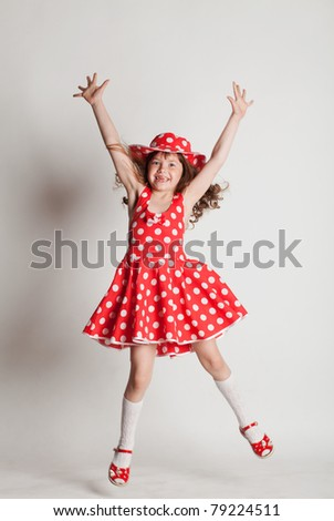 Girl in a red dress, dancing and jumping - stock photo