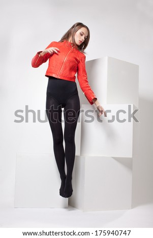 girl in a red jacket posing in studio on large white cubes - stock photo