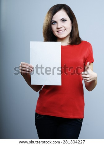 girl in a red shirt holding a poster and on the other hand shows the thumb - stock photo
