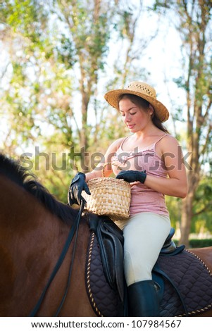 Girl in a straw hat riding a horse looking into a basket - stock photo