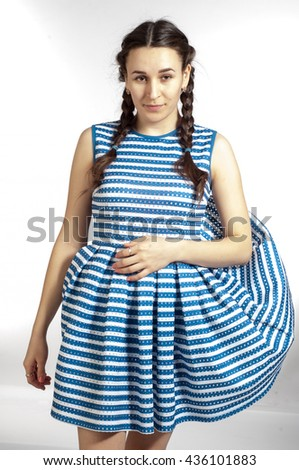 girl in a striped dress. Asian. An Asian woman in a striped skirt and top tube flash. Attractive fashion model posing in a dress in blue and white stripes - stock photo