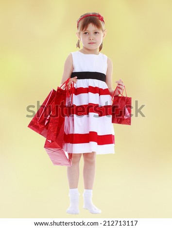 Girl in a striped dress holding red paper shopping bags.The concept of development of the child younger years. - stock photo