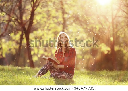 girl in a sunny park reading a book - stock photo